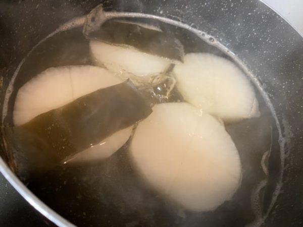 だし汁で大根を煮ます。